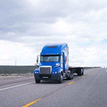 Blue Flatbed Carrier on Highway