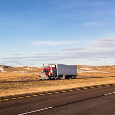 Red Semi Truckload on highway in Wyoming