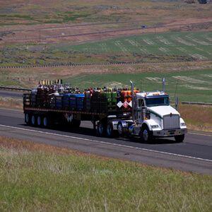 Hazmat Carrier truckload White Semi Truck carrying gas tanks
