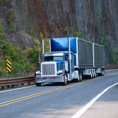 Blue semi truck on highway shipping freight from Vermont