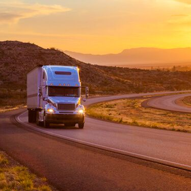 White Semi on highway during Sunset Shipping Freight from Wyoming to Florida