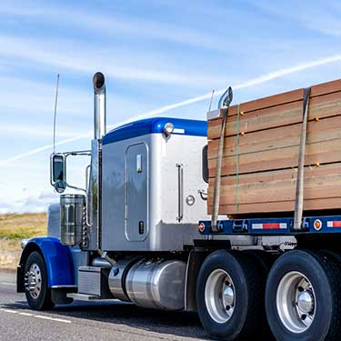 Shipping from Alaska to Washington Blue and Silver Flatbed Semi Truck carrying lumber